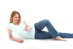 nätt reclining le för blond golvflicka arkivbilder
