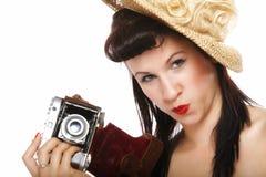 Nätt retro flicka i hatt med tappningkameran Arkivfoto