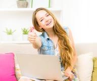 Nätt sammanträde för tonårs- flicka på soffan hemma med hennes bärbar dator arkivbild