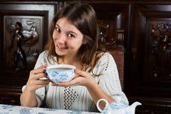 Nätt sammanträde för ung kvinna med en kopp te Fotografering för Bildbyråer