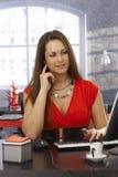 Nätt sekreterare som arbetar på skrivbordet Arkivfoto