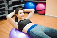 Nätt sexuell rak konditionkvinna med musculatkroppen som ligger på stor boll i sportkorridor som inomhus utbildar, horisontal arkivbild