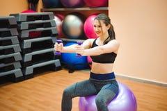 Nätt sexuell rak konditionkvinna med musculatkroppen som ligger på stor boll i sportkorridor som inomhus utbildar, horisontal royaltyfri bild
