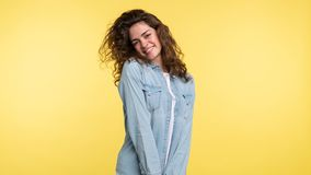 Nätt shuy brunettkvinna med lockigt hår över gul bakgrund arkivfoton