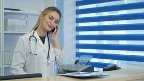 Nätt sjuksköterska som använder minnestavlan och telefonen på sjukhusmottagandeskrivbordet Royaltyfria Bilder
