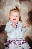 Nätt skratta liten flicka med sammanträde för blont hår på stol Arkivfoto
