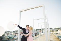 Nätt solig utomhus- stående av unga stilfulla par, medan kyssa på taket med stadssikt Royaltyfri Fotografi