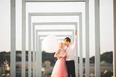 Nätt solig utomhus- stående av unga stilfulla par, medan kyssa på taket med stadssikt Arkivbilder