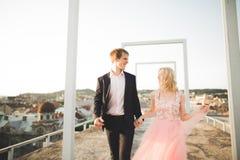 Nätt solig utomhus- stående av unga stilfulla par, medan kyssa på taket med stadssikt Fotografering för Bildbyråer