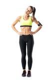 Nätt sportig flicka i gul ärmlös tröja som gör head rotation för hals som värmer övning upp Arkivfoto