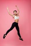 Nätt sportig kvinna i överkant och leggins som hoppar som ballerina Arkivbild
