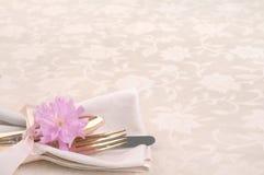 Nätt ställeinställning med gaffeln, kniv, sked, körsbärsröd blomning på kräm- bordduk royaltyfri foto