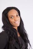 Nätt svart kvinna som ler på kameran Arkivbild