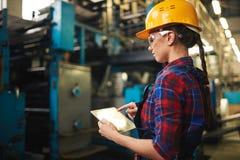 Nätt tekniker Inspecting Industrial Machine fotografering för bildbyråer