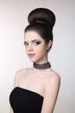 Nätt tonårig flicka med gulliga bullefrisyrer, ljus makeup, jewelr arkivfoto