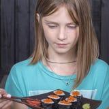 Nätt tonårig flicka med sushirulle, tonårs- flicka som äter den japanska sushi Arkivbilder