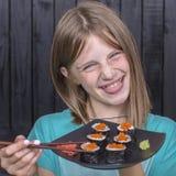 Nätt tonårig flicka med sushirulle, tonårs- flicka som äter den japanska sushi Arkivfoto