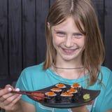 Nätt tonårig flicka med sushirulle, tonårs- flicka som äter den japanska sushi Arkivbild