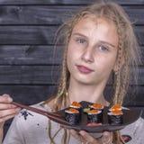 Nätt tonårig flicka med sushirulle, tonårs- flicka som äter den japanska sushi Royaltyfri Bild