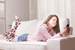 Nätt tonåringflicka som kontrollerar hennes mobiltelefon arkivfoto