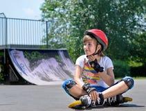 Nätt tonårs- flicka i rulle som åker skridskor kugghjulet Arkivbilder