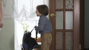 Nätt tonårs- flicka och liten broder med ryggsäcken som skriver in huset Barn ?r lyckliga att dra tillbaka hem, pojken ler lager videofilmer