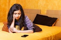 Nätt tonårs- flicka som in ligger säng se hennes telefon med sa royaltyfri foto
