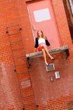 Nätt tonårs- flicka som sitter på en avsats Arkivfoto