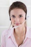 Nätt ung affärskvinna i rosa blus med hörlurar med mikrofon Arkivfoto