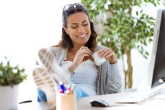 Nätt ung affärskvinna som äter yoghurt, medan ta ett avbrott i kontoret royaltyfri bild