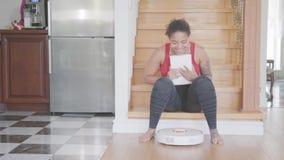 Nätt ung afrikansk amerikankvinna som sitter på trappan på det första golvet av det stora huset som smsar på hennes minnestavla m stock video