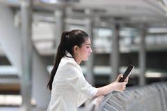 Nätt ung asiatisk kvinna som använder den mobila smarta telefonen på gatan av stadsbakgrund begreppet frambragte digitalt högt sa royaltyfri fotografi