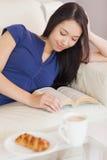 Nätt ung asiatisk kvinna som ligger på soffan som läser en bok Arkivbild