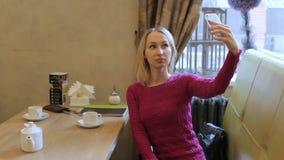 Nätt ung blond kvinnablogger som tar selfie med mobiltelefonen i kafé arkivfilmer