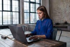 Nätt ung brunett som arbetar på bärbara datorn på trätabellen i rymlig mörk vindstudio royaltyfri fotografi