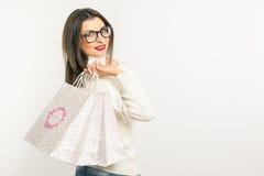 Nätt ung brunettkvinna i exponeringsglas och vita påsar för anseende för tröja hållande shoppingoch På en vit bakgrund Åtlöje upp Arkivbilder