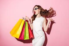 Nätt ung brunettkvinna med shoppingpåsar royaltyfri bild