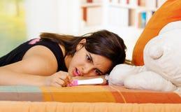 Nätt ung brunettkvinna som ner ligger med det främsta havandeskaphemprovet, intensiv emotionell stirrande, trädgårds- fönster arkivfoton