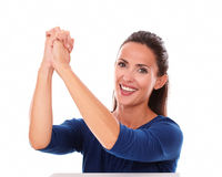 Nätt ung dam i blå skjorta som gör en gest att segra Fotografering för Bildbyråer