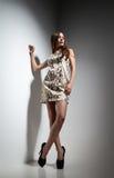 Nätt ung dam i klänning över grå bakgrund Royaltyfria Bilder