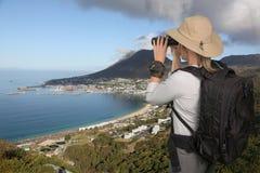 Nätt ung dam med en solhatt som tycker om den kust- sikten Arkivfoton