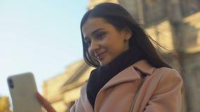 Nätt ung dam som gör selfie nära gammal byggnad, populär touristic destination stock video