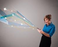 Nätt ung dam som rymmer en telefon med färgrika abstrakta linjer  Royaltyfria Foton