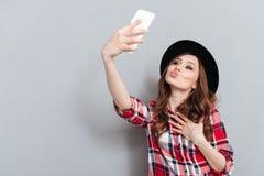 Nätt ung dam som talar av mobiltelefonen som blåser kyssar Royaltyfria Foton