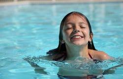 Nätt ung flicka i en simbassäng Arkivbild