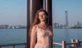 Nätt ung flicka i härligt klänninganseende på pelaren på solnedgång royaltyfri foto