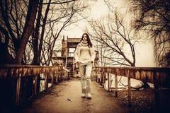 Nätt ung flicka som är utomhus- på den gamla bron Royaltyfri Foto