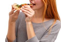 Nätt ung flicka som äter smaklig pizza som isoleras på en vit bakgrund olivgrön för olja för kök för kockbegreppsmat ny över häll arkivbild