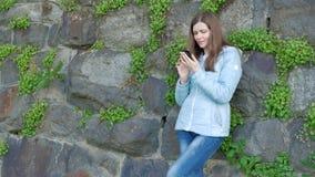 Nätt ung flicka som använder smartphonen Tappningvägg av den lösa stenen i bakgrunden arkivfilmer
