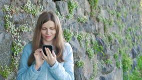 Nätt ung flicka som använder smartphonen Tappningvägg av den lösa stenen i bakgrunden stock video